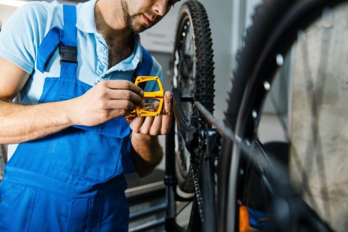 meccanico smonta un pedale da una bicicletta