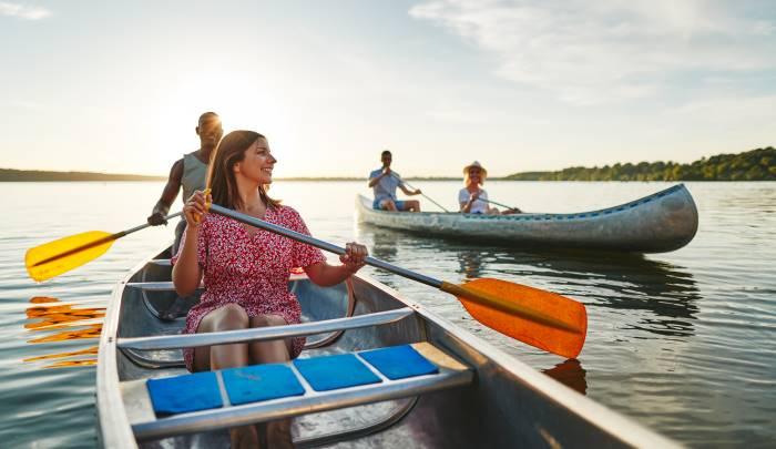 Qual è la differenza canoa kayak? Persone remando in canoa in un lago