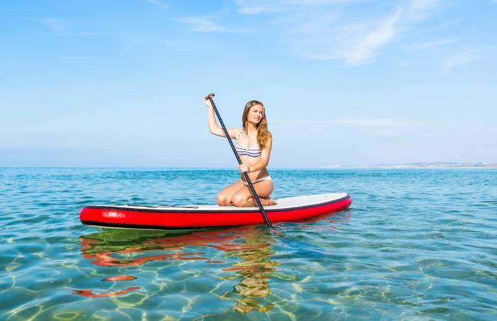 Una ragazza utilizzando un paddle surf gonfiabile